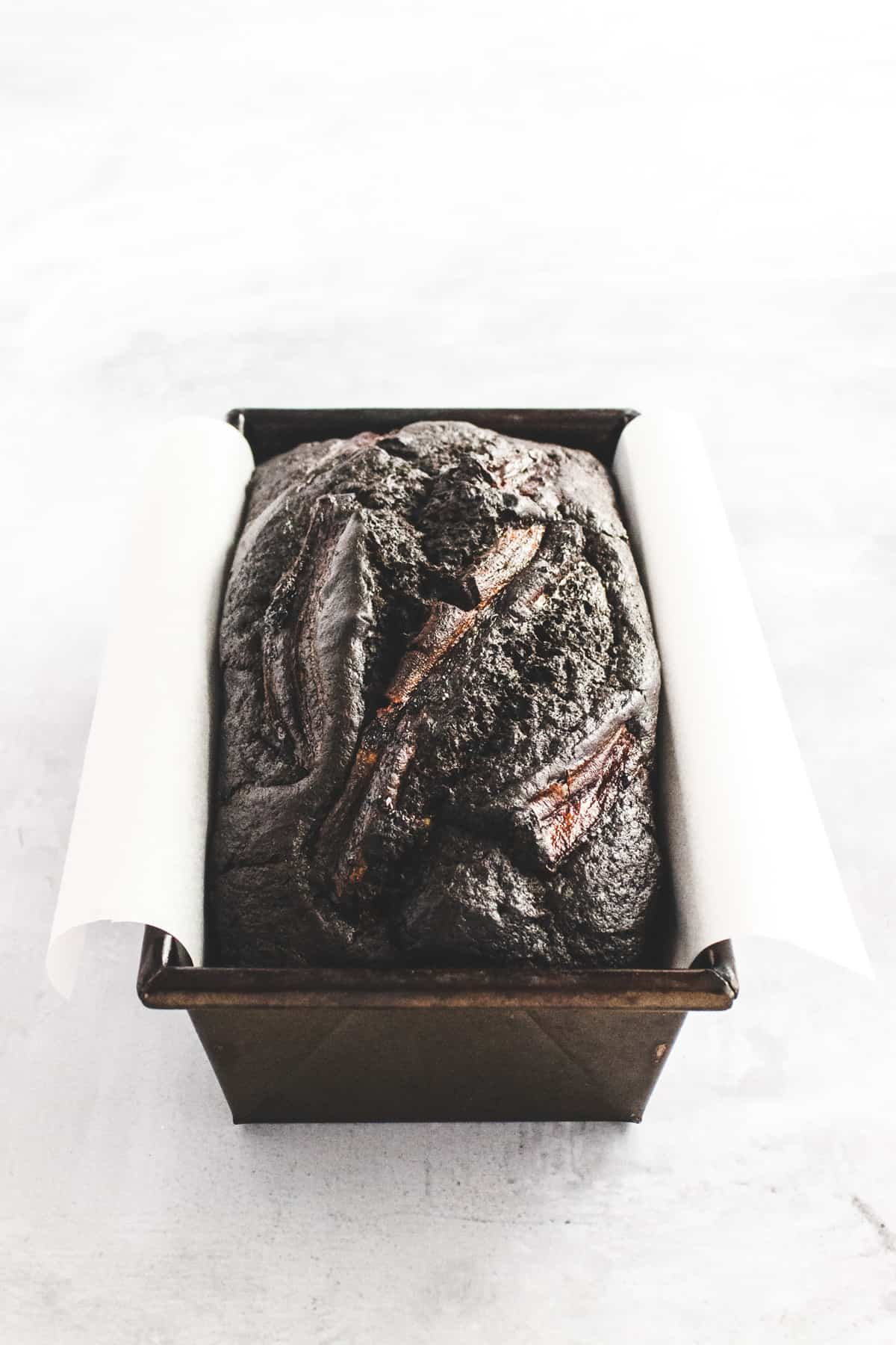 Dark chocolate banana bread in a loaf tin lined with baking parchment